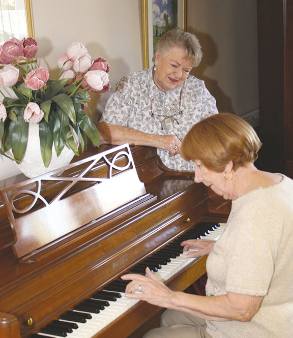 Ladies enjoying playing the piano at their independent living home in Tucson, AZ