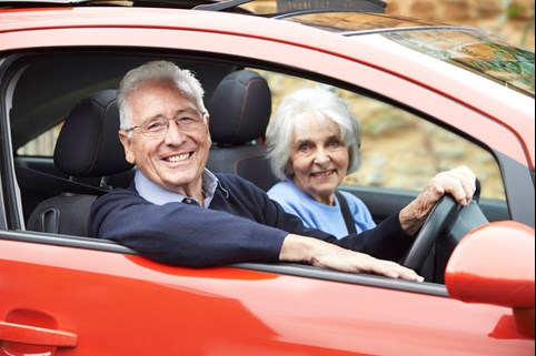 Elderly couple safely driving a vehicle