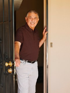 Independent living resident opening his security screen door in his senior living apartment at Fellowship Square Tucson