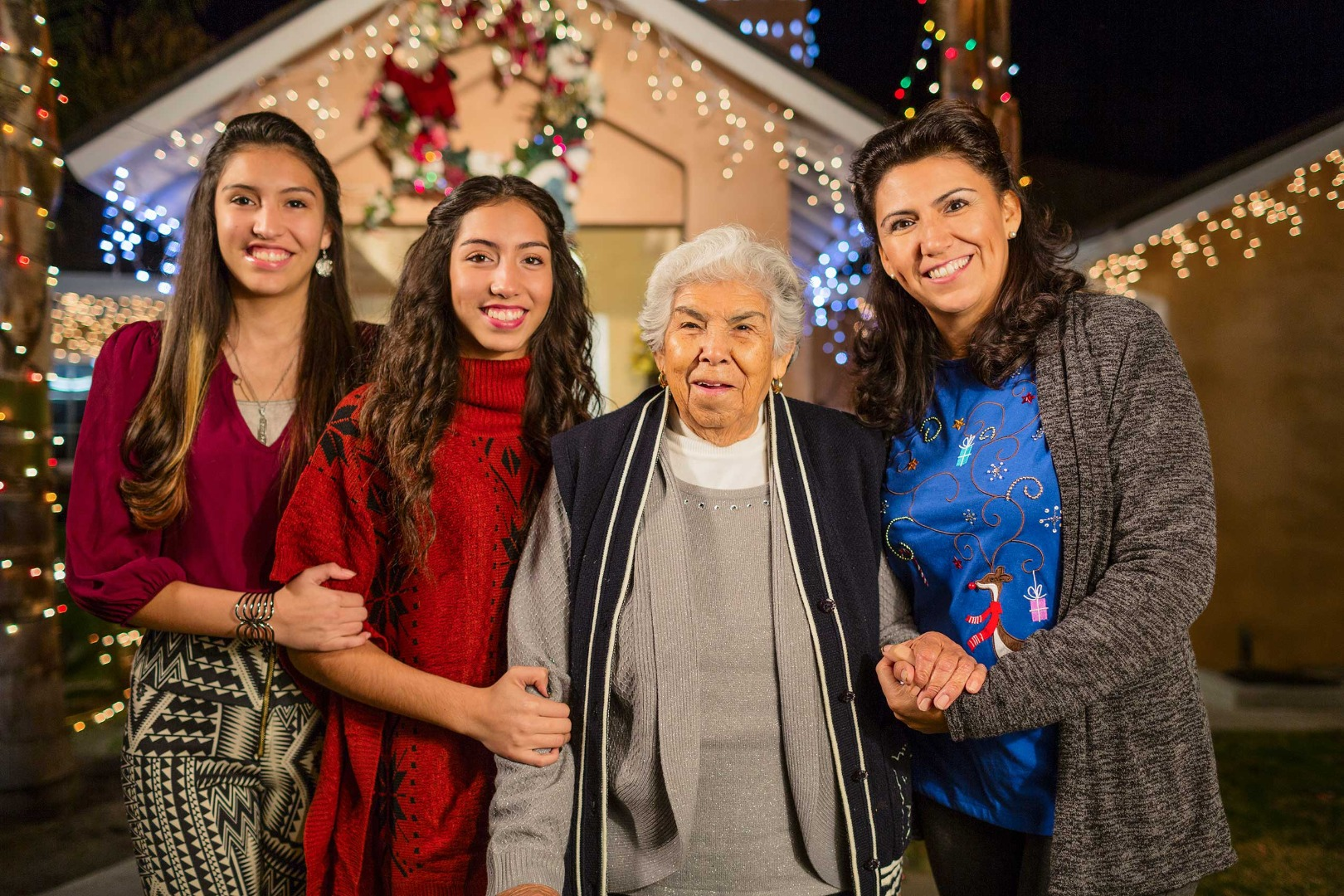 Grandmother with her daughter and granddaughters standing together during the Christmas season.